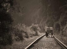 three people walking along a railway track