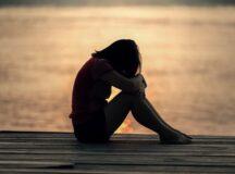 sad girl next to lake
