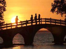 People on bridge at sunset