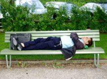 Businessman sleeping on park bench