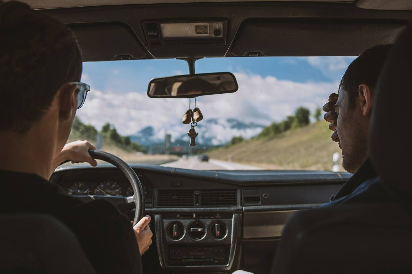 Two male friends driving in car