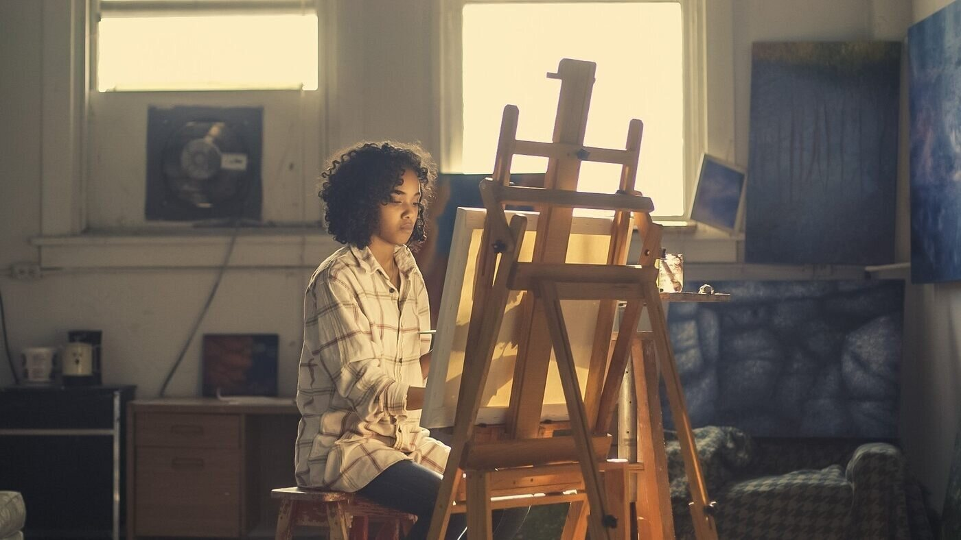 Artist painting at easel on canvas